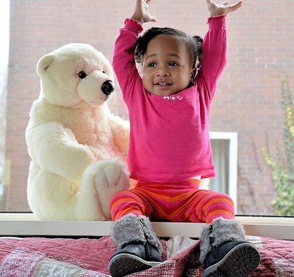 small girl on blanket with stuffed bear